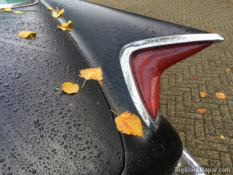 Autumn leaves on rear fender trunk of a black 1960 Chrysler NewYorker